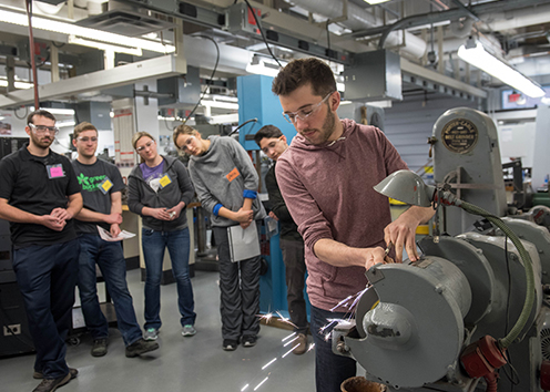 Engineering students watch as part is machined.