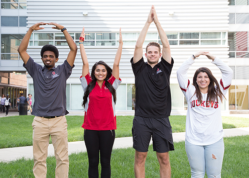 Four engineering students pose in O-H-I-O pose outside of Scott Laboratory.
