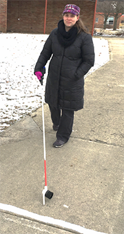 Mary Ball-Swartwout holds a cane near a strip of smart paint while walking along a sidewalk.