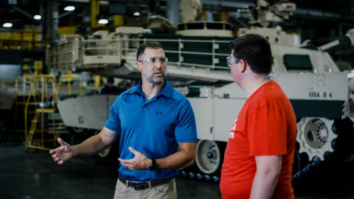A tank is visible in the background as an engineer gestures while talking to an Ohio State student.