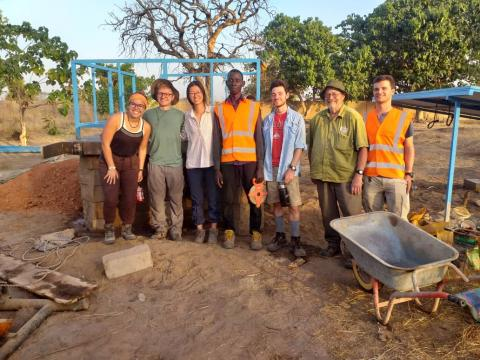 Students and their advisor pose with a Gambian man on the project site.